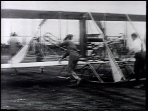 men pushing 'wright flyer' army signal corps airplane no 1 'benny' foulois w/ unidentified man next to aircraft biplane taking off flying [vo retired... - 1910 stock-videos und b-roll-filmmaterial