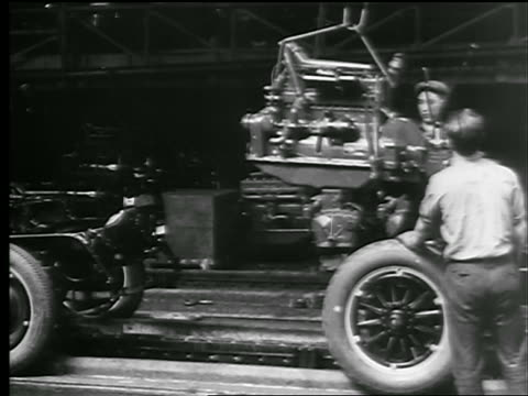 stockvideo's en b-roll-footage met b/w 1927 men putting engine in car on assembly line in factory / new york state - autofabriek