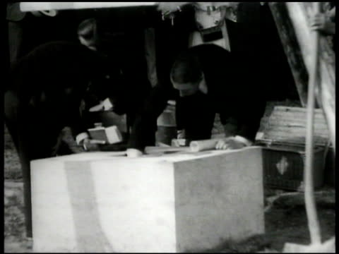 men putting papers into cornerstone block. int carrying sandbag, hall under construction. scaffolding. ext building, peacocks fg. int man working by... - vereinte nationen stock-videos und b-roll-filmmaterial