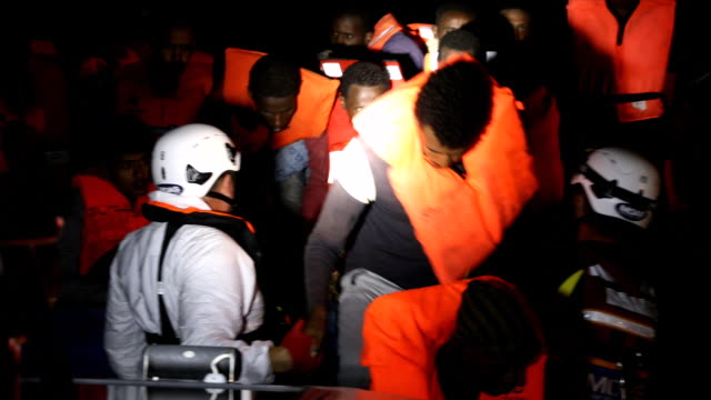 men queue to get onto a rescue craft from a wooden boat, as members of moas, migrant offshore aid station make resues on november 22, 2016 in... - rescue stock videos & royalty-free footage