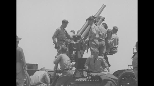 men quickly firing field guns a line of men shooting with machine guns / puffs of smoke in the sky / several men hurry to load a large cannon /... - military exercise stock videos & royalty-free footage