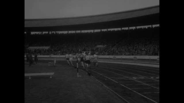 vs men race around track audience in stands flashbulbs go off as winner crosses finish line / view from behind spectators holding umbrellas men race... - men's track stock videos and b-roll footage