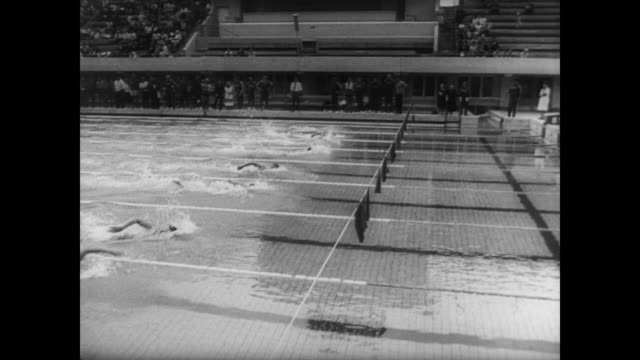 Men race in swimming pool in front of crowd / Don Schollander wins wins both the 100 and 100meter men's freestyle events