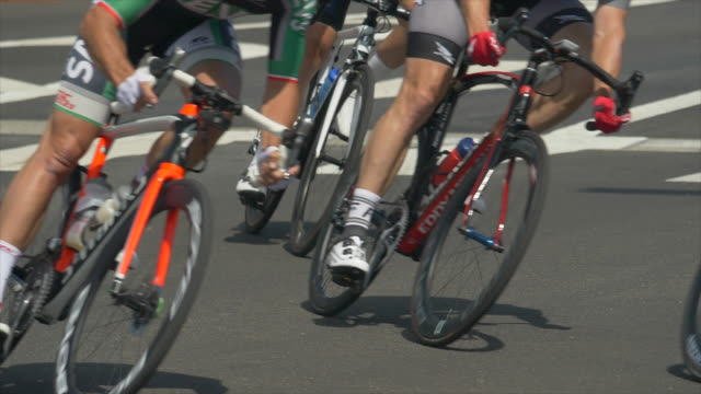 men racing around a corner curve in a road bike bicycle race. - slow motion - ロードサイクリング点の映像素材/bロール