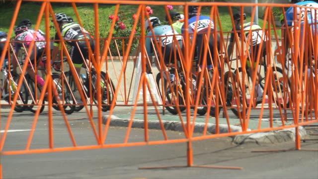 men racing around a corner curve in a road bike bicycle race. - slow motion - プロトン点の映像素材/bロール