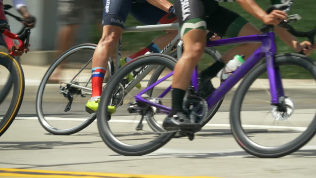 men racing around a corner curve in a road bike bicycle race. - slow motion - curve stock videos & royalty-free footage