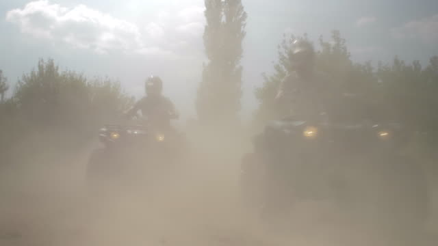 men racing atv quad motocross motorcycles vehicles on a dirt off road. - slow motion - off road racing stock videos & royalty-free footage