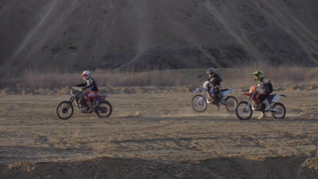 men racing motocross motorcycles on a dirt off road. - slow motion - off road racing stock videos & royalty-free footage