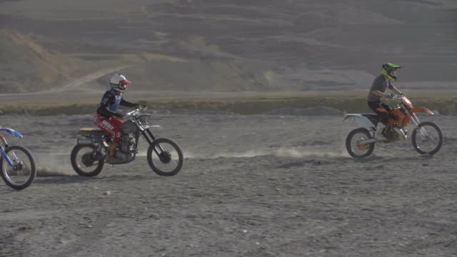 men racing motocross motorcycles up a hill on a dirt off road. - slow motion - off road racing stock videos & royalty-free footage