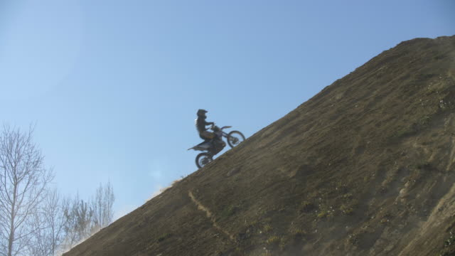 men racing motocross motorcycles up a hill on a dirt off road. - hill点の映像素材/bロール