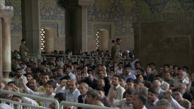 MS ZI PAN Men raising arms during Friday prayers in Imam Mosque, Esfahan, Iran