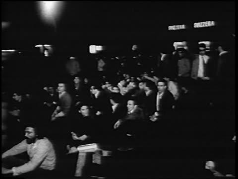 b/w 1967 men raising fists at sitdown antiwar demonstration at night / rome italy / newsreel - anno 1967 video stock e b–roll