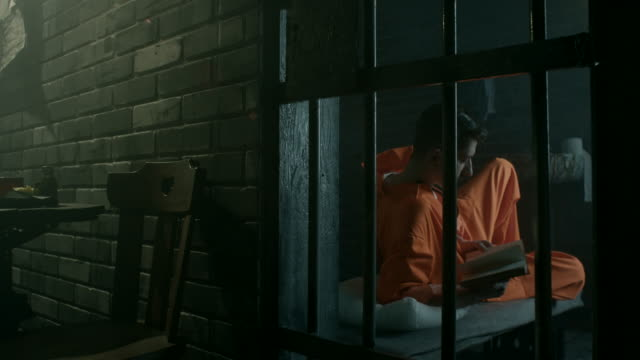 Men reading book in prison cell