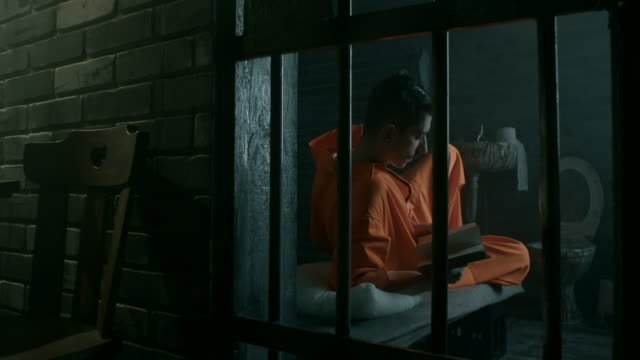 men reading book in prison cell - prisoner orange stock videos & royalty-free footage