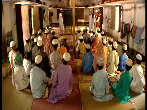 vídeos de stock, filmes e b-roll de men receive religious instruction at madrassa - madressa