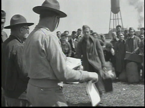 men receiving papers from man in uniform / recruits walking across field, carrying luggage / man reading forms - 1934 stock videos & royalty-free footage