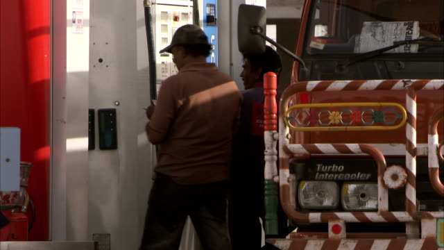 men refuel a truck and count money on a petrol station forecourt. - fuel pump stock videos and b-roll footage