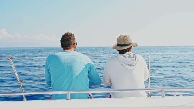 4 k männer entspannen und reden auf sonnigen segelboot am blauen ozean, real-time - zeigen stock-videos und b-roll-filmmaterial