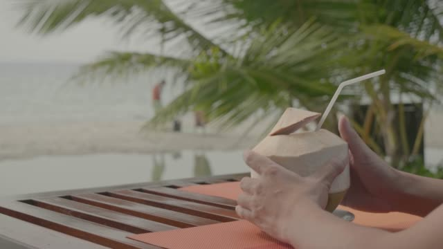 men relaxing at beach on chair with drinking coconut juice. - outdoor chair stock videos & royalty-free footage