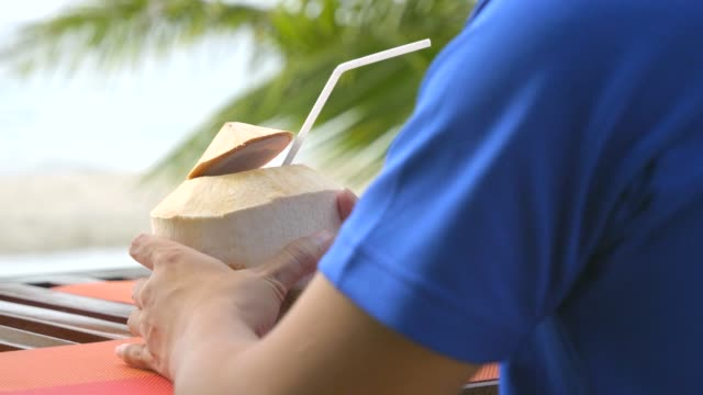 men relaxing at beach on chair with drinking coconut juice. - coconut palm tree stock videos & royalty-free footage