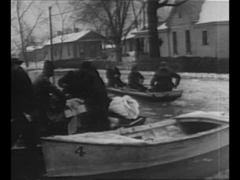 men remove bundles from rowboat in foreground as boat with passengers approaches in flooded street during ohio river valley flood / girl winces as... - 1937 stock videos and b-roll footage