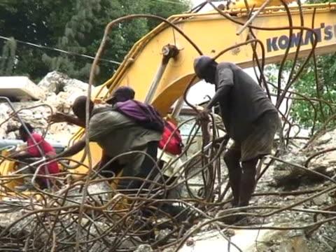vídeos de stock e filmes b-roll de men remove copper and other materials from large pile of rubble following devastating earthquake haiti 10 march 2010 - hispaniola