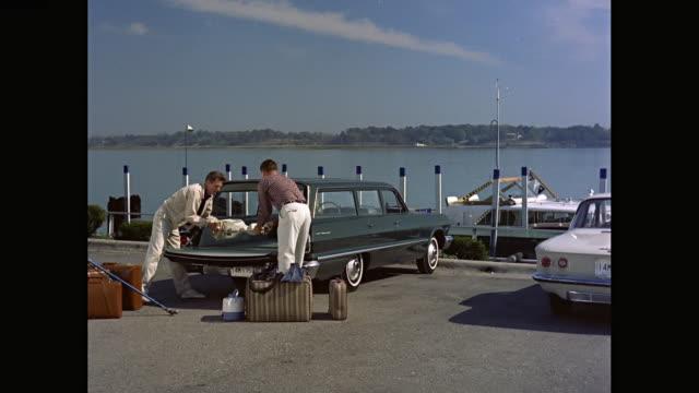 vídeos de stock e filmes b-roll de ws men removing scuba diving equipment from 1963 chevrolet station wagon car / united states - aqualung diving equipment