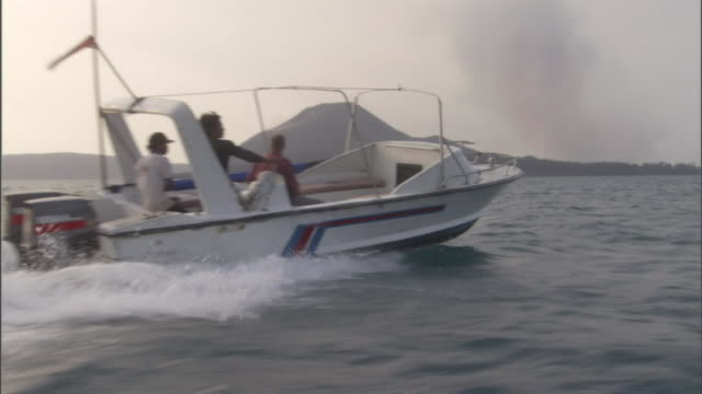 men ride a speedboat near a volcano. - schnellboot stock-videos und b-roll-filmmaterial