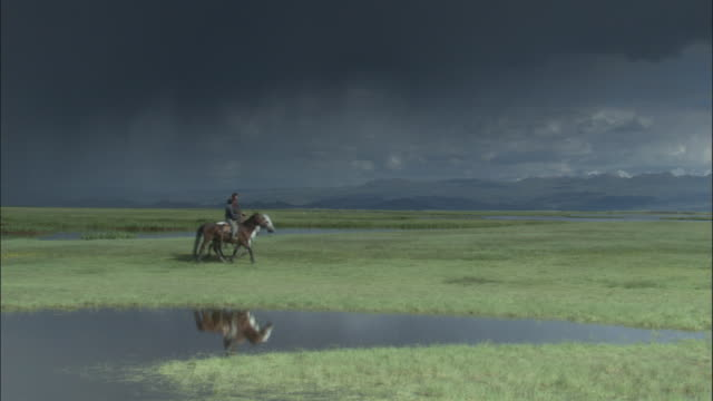 Men ride horses across grassland under a stormy sky, Bayanbulak grasslands.