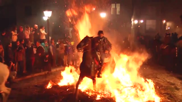 Men ride horses through a bonfire during 'Las Luminarias' Festival on January 16 2018 in San Bartolome de Pinares Spain In honor of Saint Anthony the...