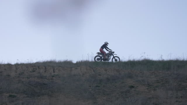 Men riding and jumping motocross motorcycles on a dirt off road. - Slow Motion