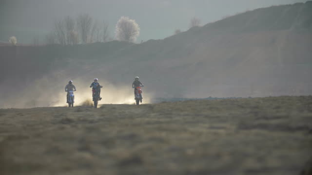 Men riding and racing motocross motorcycles in a race on a dirt off road. - Slow Motion