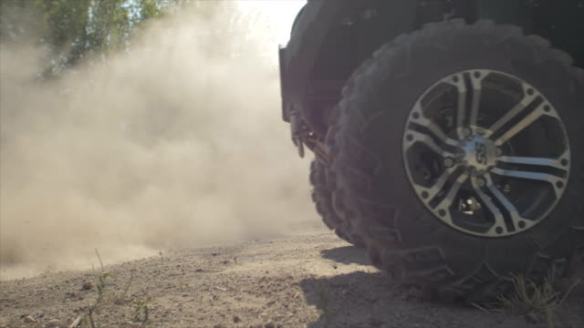 stockvideo's en b-roll-footage met men riding and wheels spinning atv quad motocross motorcycles vehicles on a dirt off road. - slow motion - men