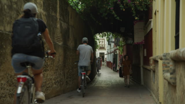 vidéos et rushes de men riding bicycle passing woman walking on narrow sidewalk / seville, sevilla, spain - étroit