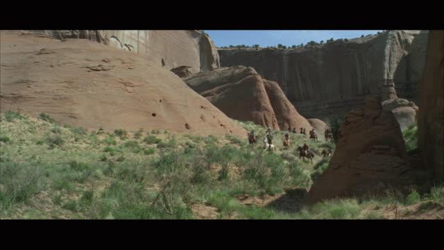 WS PAN Men riding horse through canyon