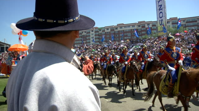 men riding horses and wearing costumes parading at naadam festival - animale da lavoro video stock e b–roll