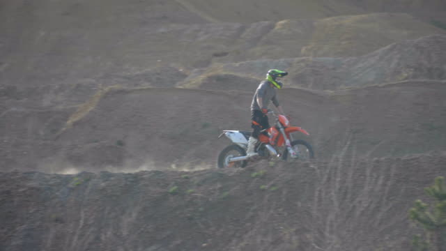 Men riding motocross motorcycles on a dirt off road quarry. - Slow Motion