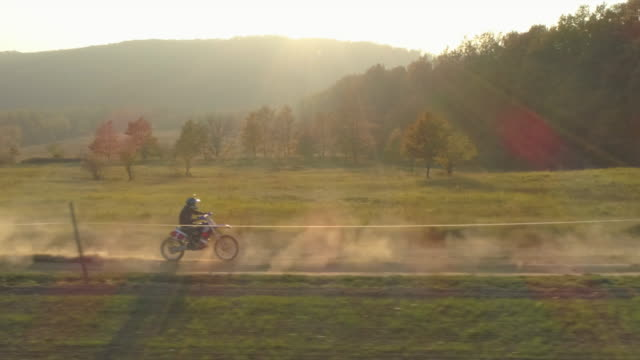 men riding motocross motorcycles on a dirt off road. - slow motion - dusk stock videos & royalty-free footage