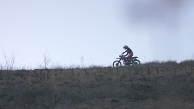 Men riding motocross motorcycles on a dirt off road. - Slow Motion