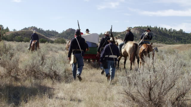 vídeos de stock, filmes e b-roll de ws men riding on horse and wagons walking on grassy landscape / montana, united states  - carroça