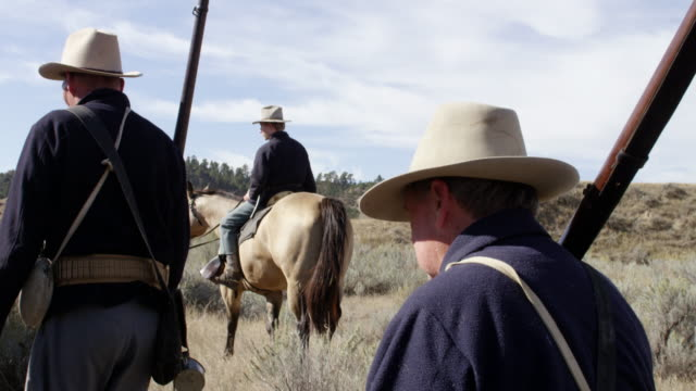 vídeos y material grabado en eventos de stock de ws reenactment men riding on horse and wagons walking on grassy landscape / montana, united states - grupo mediano de animales