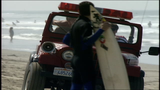 men riding on lifegaurd jeep on beach in huntington ca - water sports equipment stock videos and b-roll footage