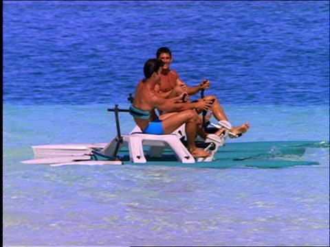 2 men riding pedalboats on ocean / Cancun