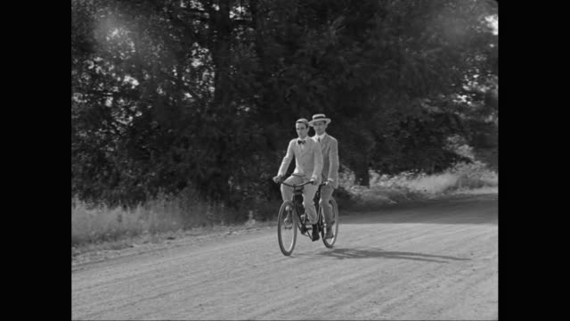 ws pan men riding tandem bicycle on dirt road / united states - tandem stock videos & royalty-free footage