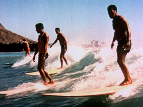 1960 POV MONTAGE men riding wave on surfboards / group riding wave in outrigger / Diamond Head in background / Honolulu, Hawaii, USA