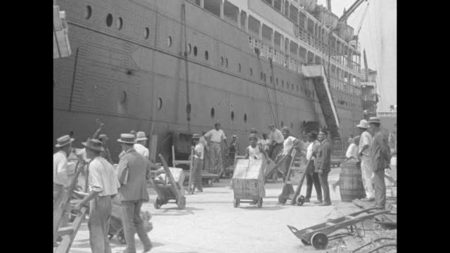 vidéos et rushes de men rolling barrels to courtyard / vs activity on dock with barrels being offloaded / an area with a vast number of barrels and a tracking shot of... - prohibition