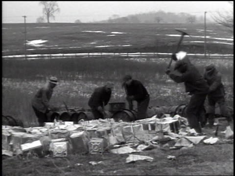 vidéos et rushes de men rolling metal drums, cans, from distillery barn onto back of flatbed truck, men working around barn, carrying out square tin cans, destroying... - prohibition