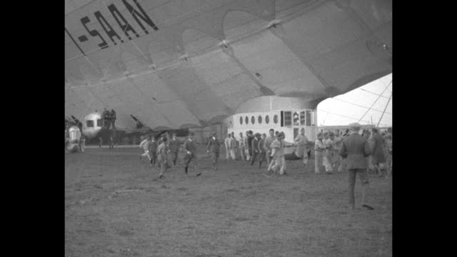 men run along under the 'i-saan' airship with the gondola at ground level; the ground crew holds ropes to anchor the airship / the ship floats from a... - megaphone stock videos & royalty-free footage
