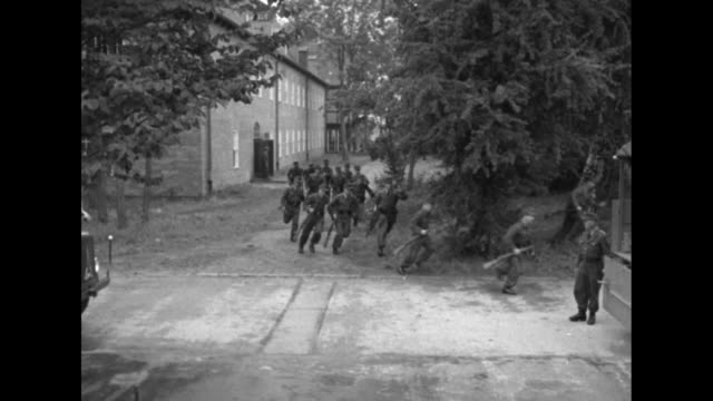 men run from building and jump into transport trucks as others look over document - 1951 stock-videos und b-roll-filmmaterial
