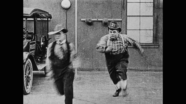 1920 men (fatty arbuckle and buster keaton) run into a pole while wheeling a firehose through town, and then run back to the garage to get fire hats - fatty arbuckle stock videos and b-roll footage